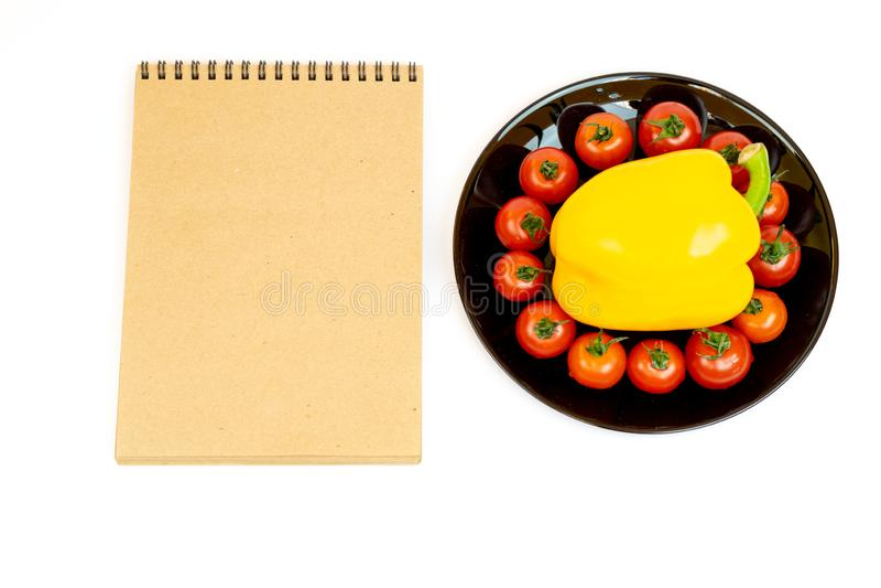 Gele paprika met tomaten in een zwarte plaat die op witte achtergrond dichtbij Blocnote wordt ge?soleerd Samenstelling van geel p stock afbeeldingen