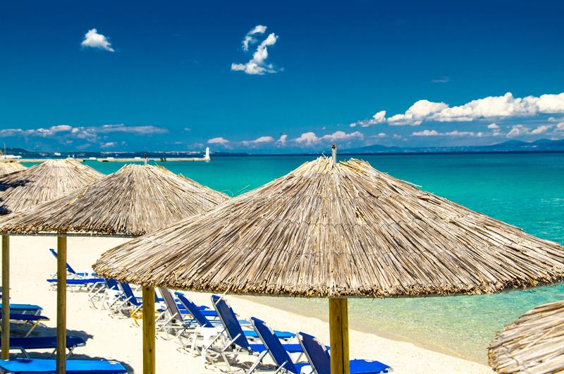 Gele paraplu's op strand, blauw paradijswater, Halkidiki, Greec stock afbeelding