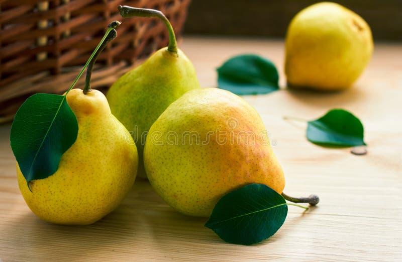 Gele peren met groene bladeren die op houten lijst voor rieten mand leggen royalty-vrije stock foto's