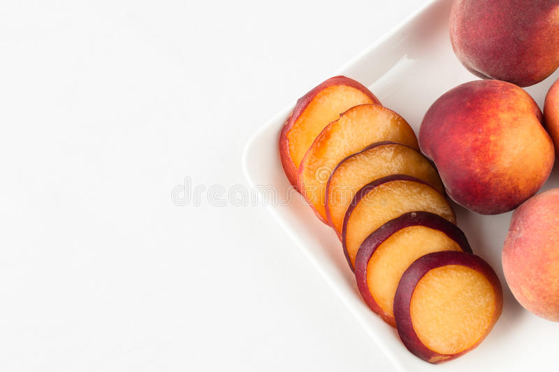Gele perziken op witte vierkante plaat stock foto's