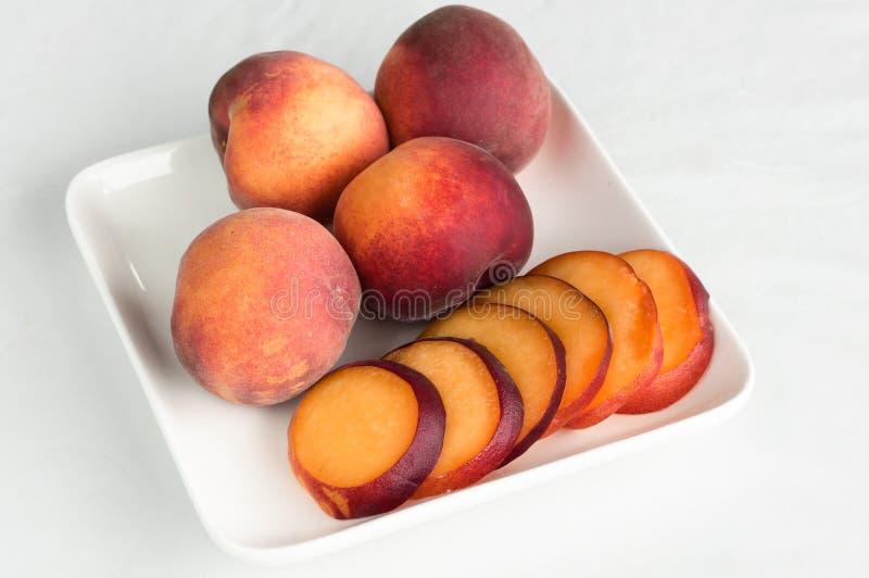 Gele perziken op witte vierkante plaat royalty-vrije stock fotografie