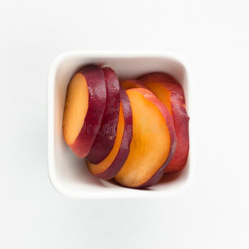 Gele perziken in witte vierkante kom stock afbeeldingen