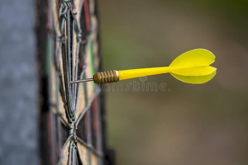 Gele pijltjepijl die in het doel van dartboardzaken su raken stock afbeeldingen