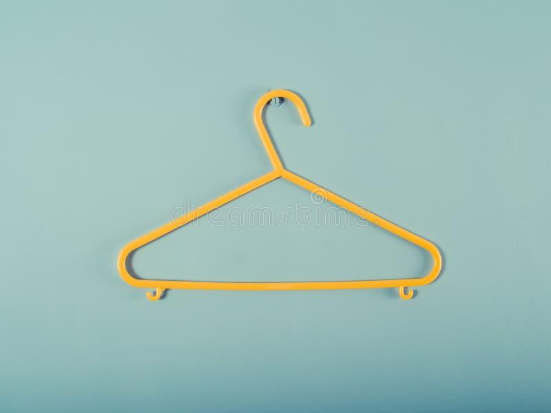 Gele plastic hanger op een blauwe muur royalty-vrije stock afbeeldingen