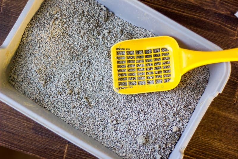 Gele plastic lepel op de grijze die kattebak, door blauw draagstoelzand wordt gevuld royalty-vrije stock foto
