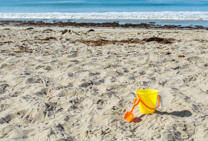 Gele plastic zandemmer met oranje schop bij een zandig strand stock afbeelding