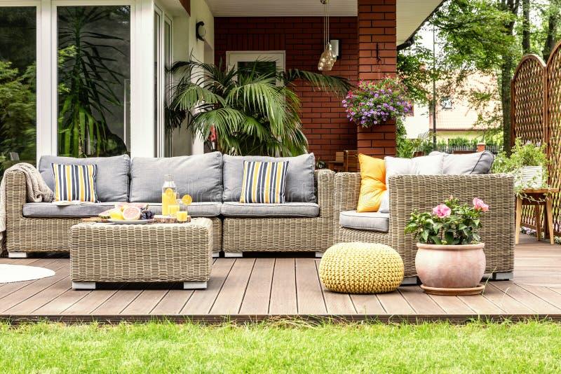 Gele poef en bloemen naast het meubilair van de rotantuin op woode stock afbeeldingen