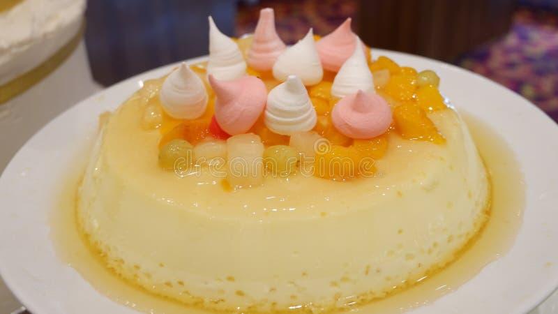 Gele pudding met spiraalvormige room op witte plaat stock foto's