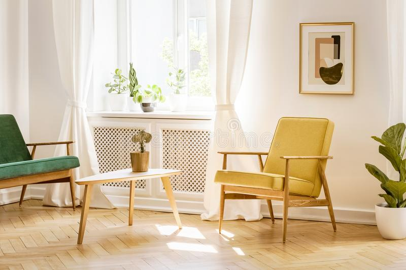 Gele, retro leunstoel en een groene bank door een groot, zonnig venster i stock foto's