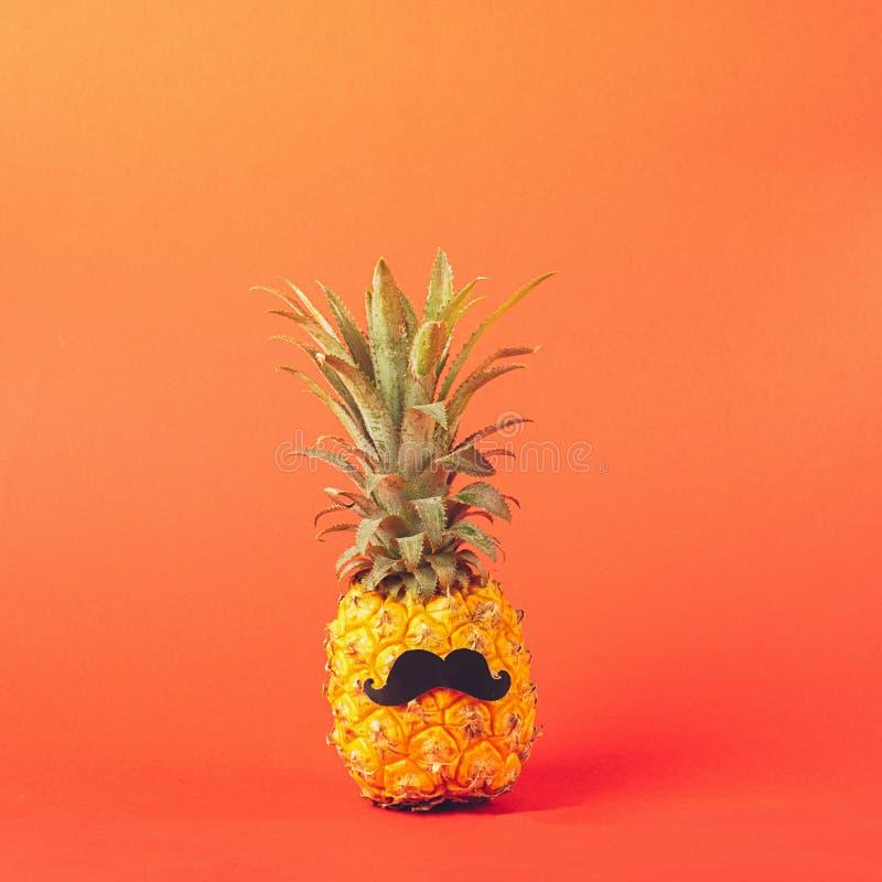 Gele rijpe ananas met zwarte snor op een rode achtergrond Grappig gezicht van een tropisch fruit De ruimte van het conceptenexemp stock foto's