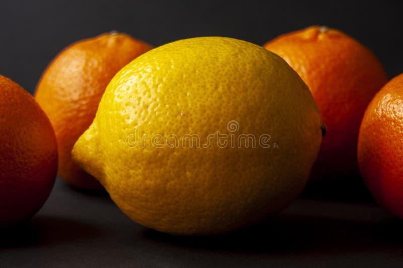 Gele rijpe citroen met vier mandarijntjes op de achtergrond o stock foto