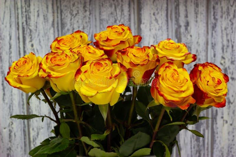 Gele rozen in een metaalvaas op een houten muurachtergrond stock fotografie