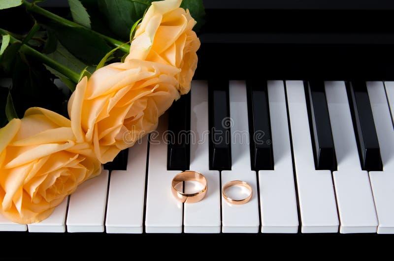 Gele rozen met trouwringen op de piano Het voorbereidingen treffen voor het huwelijk Een gift aan uw geliefd voor een een huwelij stock afbeeldingen