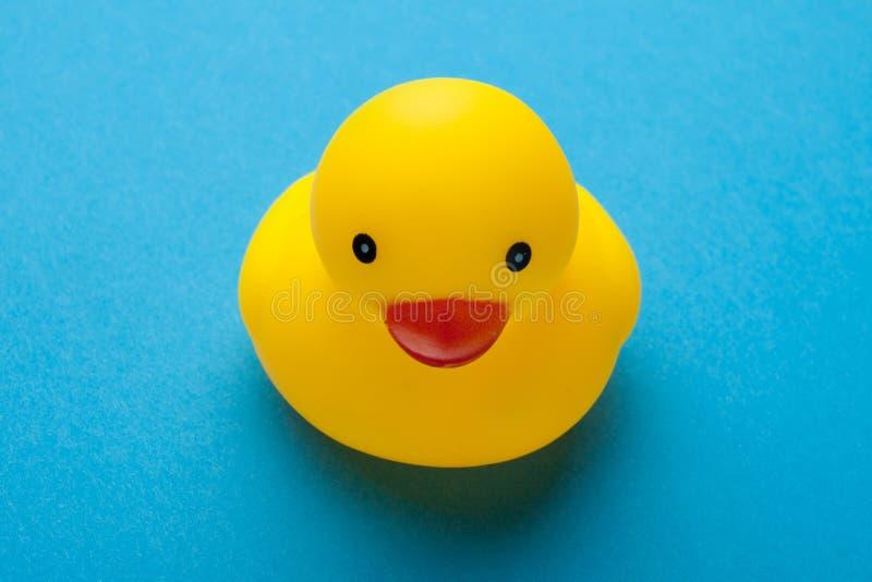 Gele rubberstuk speelgoed eend die op blauwe achtergrond wordt geïsoleerd stock foto's