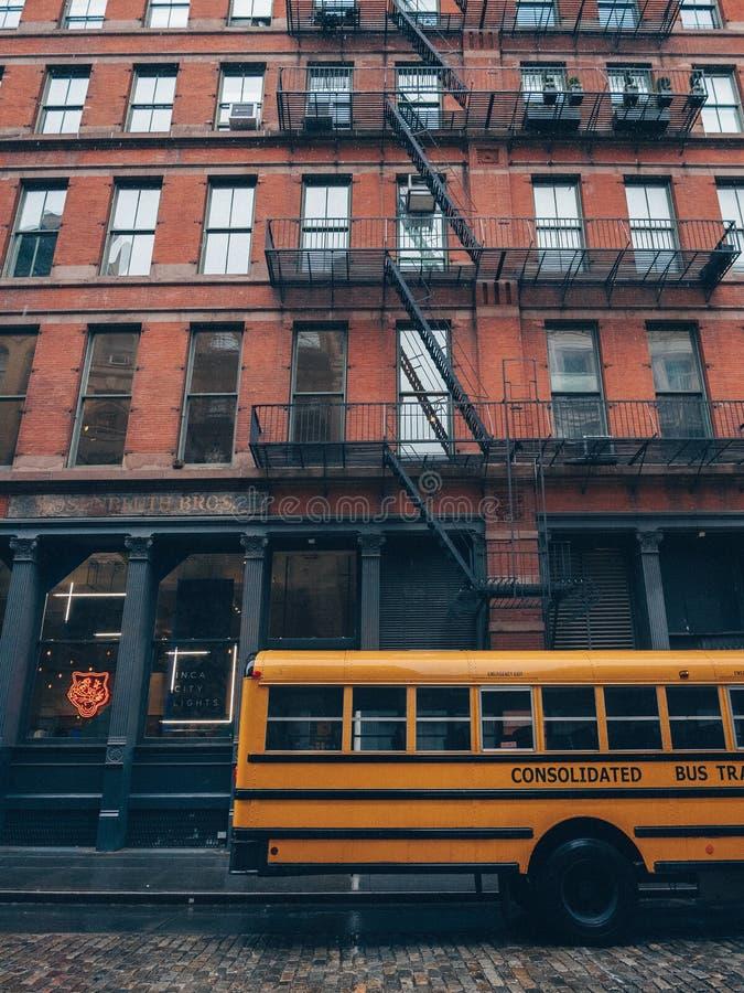 Gele schoolbus bij een wolkenkrabber royalty-vrije stock foto