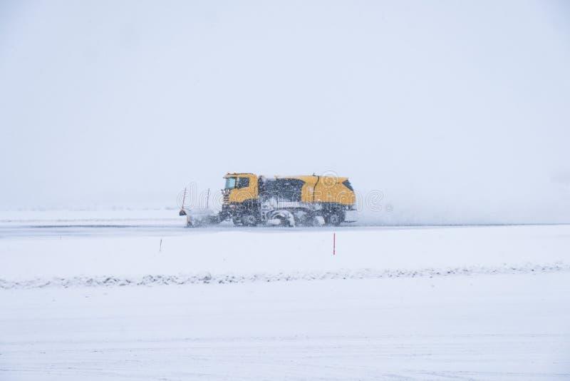 Gele sneeuwploegen die de weg van de sneeuwdekking in blizzard ploegen stock afbeelding