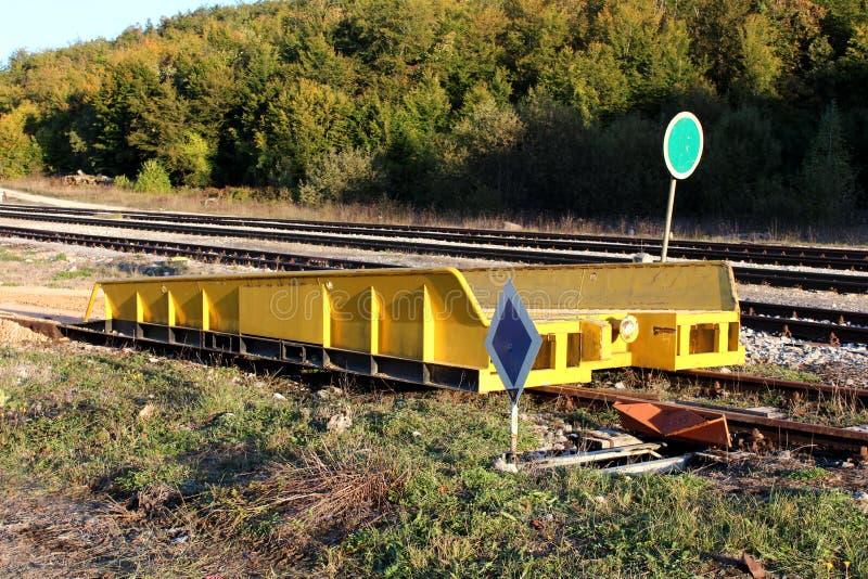 Gele sterke de ladingshelling van de metaalspoorweg opgezet op spoorwegsporen naast het omringde mechanisme en het waarschuwingsb royalty-vrije stock fotografie