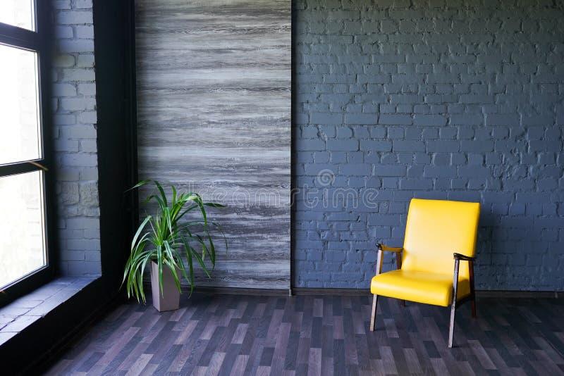 Gele stoel dichtbij venster in modern donker binnenland met zwarte bakstenen muur, exemplaarruimte stock foto's