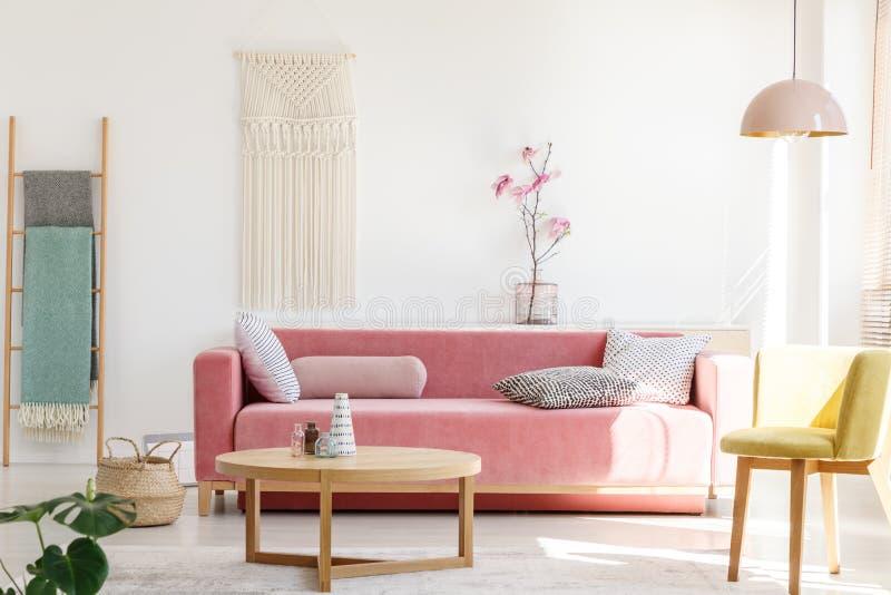 Gele stoel naast roze bank en houten lijst in pastelkleur het leven stock afbeelding