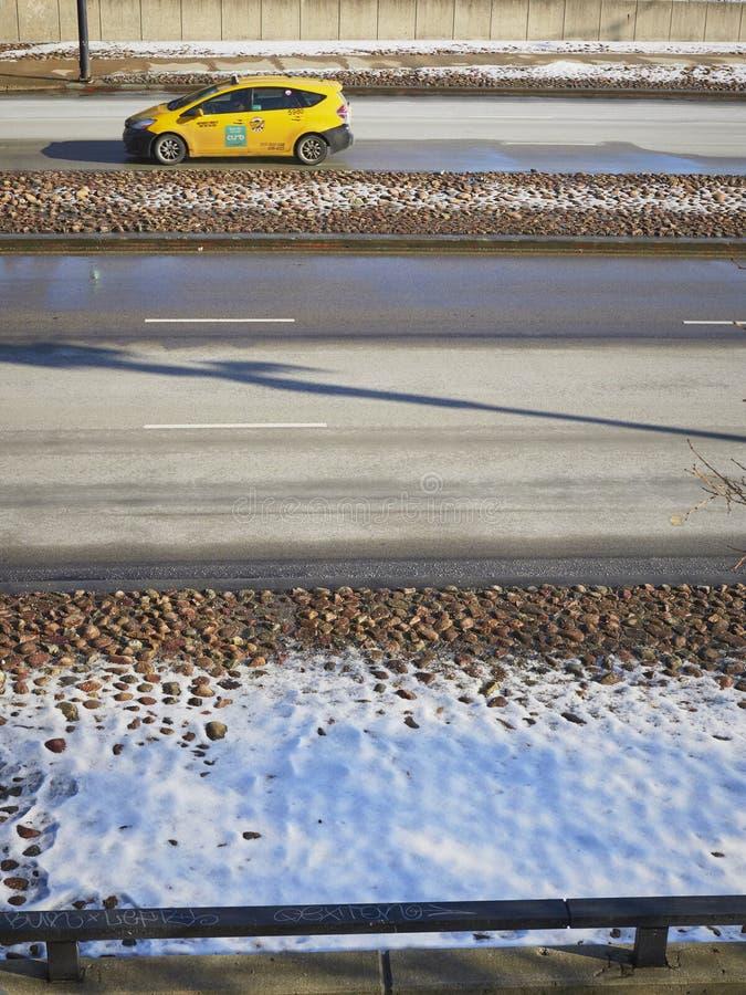 Gele Taxiauto op weg lichte sneeuw behandelde grond royalty-vrije stock afbeeldingen