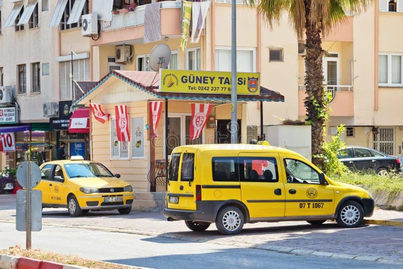 Gele taxistandplaatsen door de kant van de weg van de betonmolens die op passagiers wachten stock afbeelding