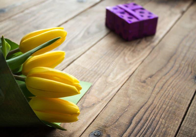 Gele tulpen en gift op een houten achtergrond stock foto