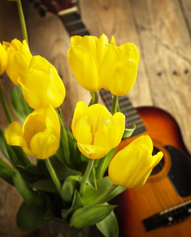 Gele tulpen en gitaar op oude houten oppervlakte royalty-vrije stock fotografie