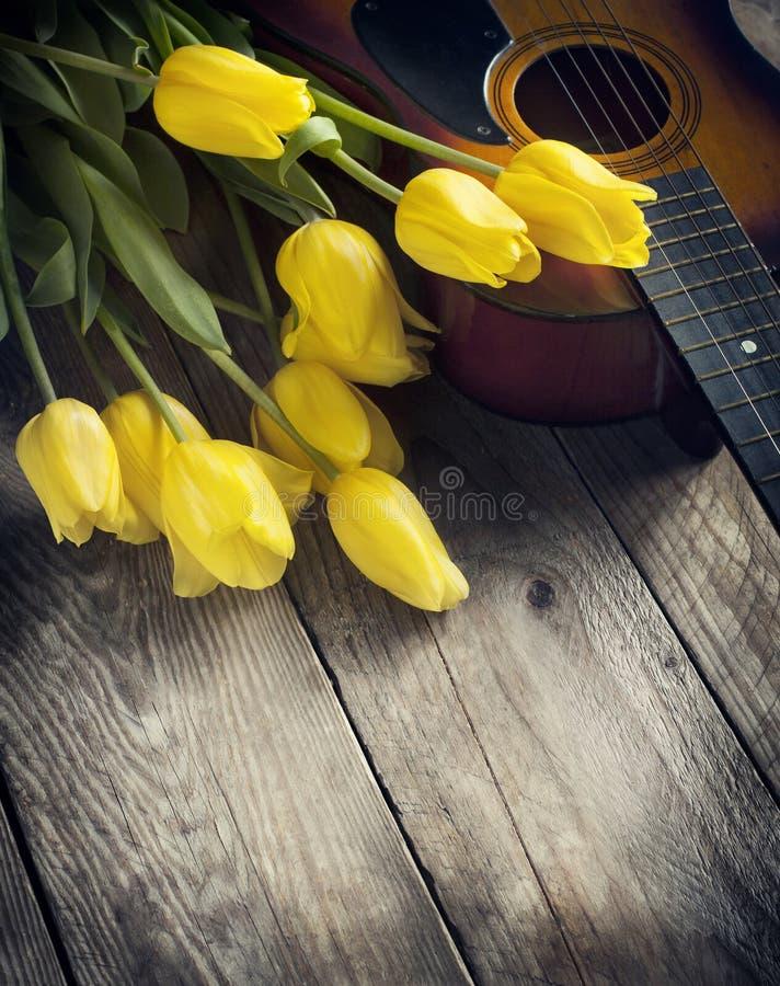 Gele tulpen en gitaar op oude houten oppervlakte stock afbeeldingen