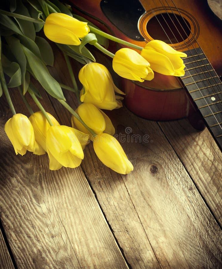 Gele tulpen en gitaar op oude houten oppervlakte Kleine diepte van fie stock foto's