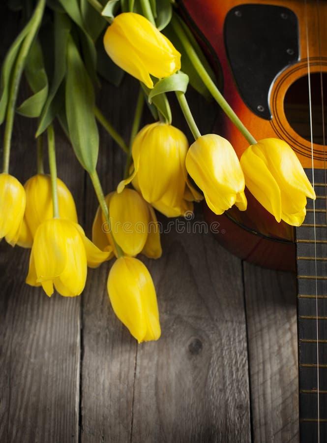 Gele tulpen en gitaar op oude houten oppervlakte Kleine diepte van fie royalty-vrije stock foto