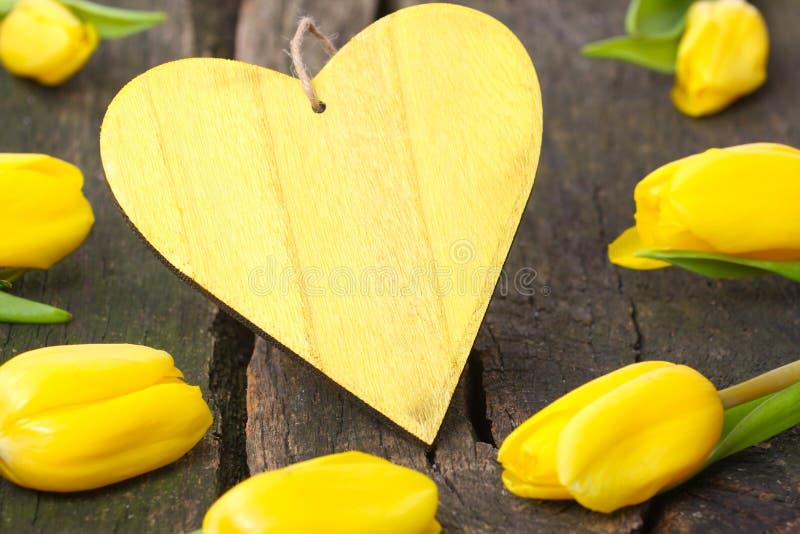 Gele tulpen rond een houten hart royalty-vrije stock fotografie