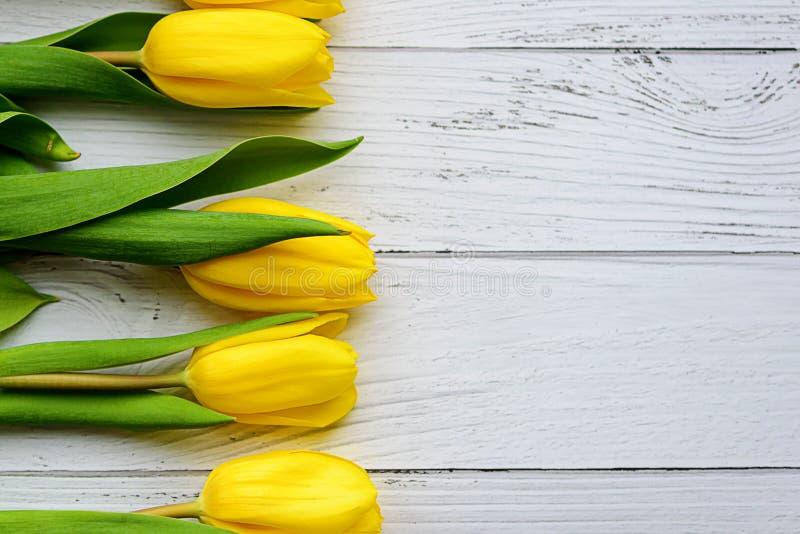 Gele tulpenbloemen op witte houten achtergrond Het wachten op de lente De dag van de gelukkige moeder, 8 Maart Vlakke positie, ho stock afbeelding