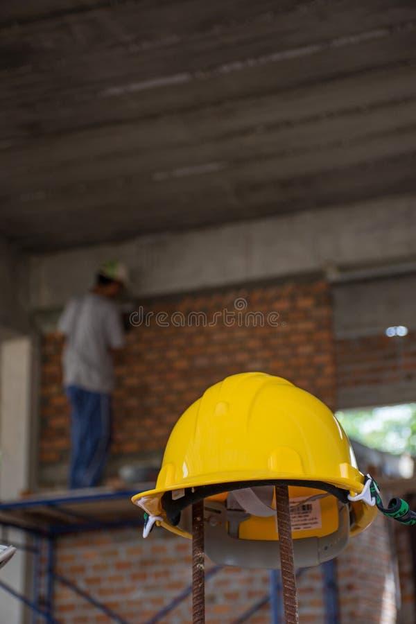 Gele veiligheidshelm met bouwvakker die bakstenen plaatsen stock fotografie