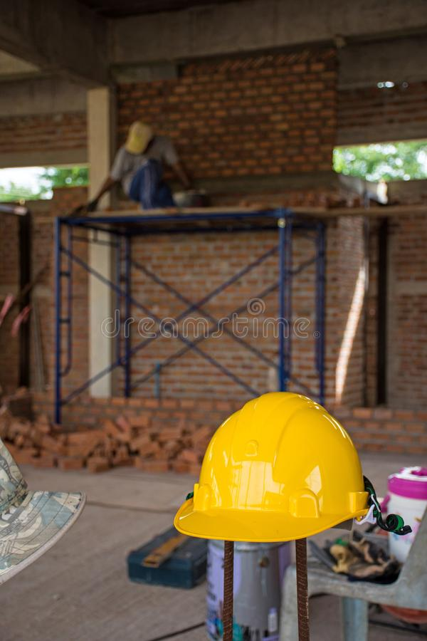 Gele veiligheidshelm met bouwvakker die bakstenen plaatsen stock foto's