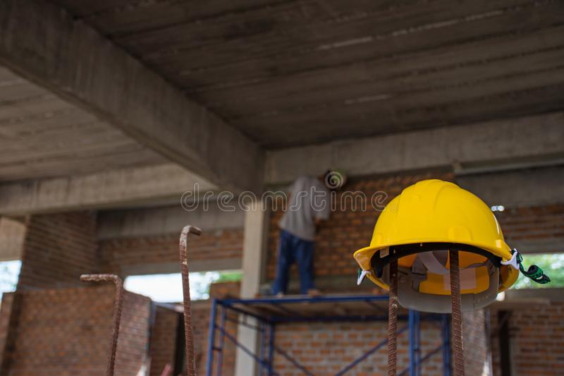 Gele veiligheidshelm met bouwvakker die bakstenen plaatsen stock foto