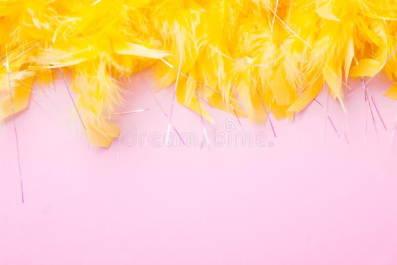 Gele Veren op roze achtergrond Feestelijk en vakantie stock foto