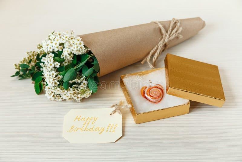 Gele Verjaardagskaart met Gouden Huidige Doos met Glashart Boeket Witte Kleine Bloemen in Bruin Ambachtdocument met Koord wit stock foto's