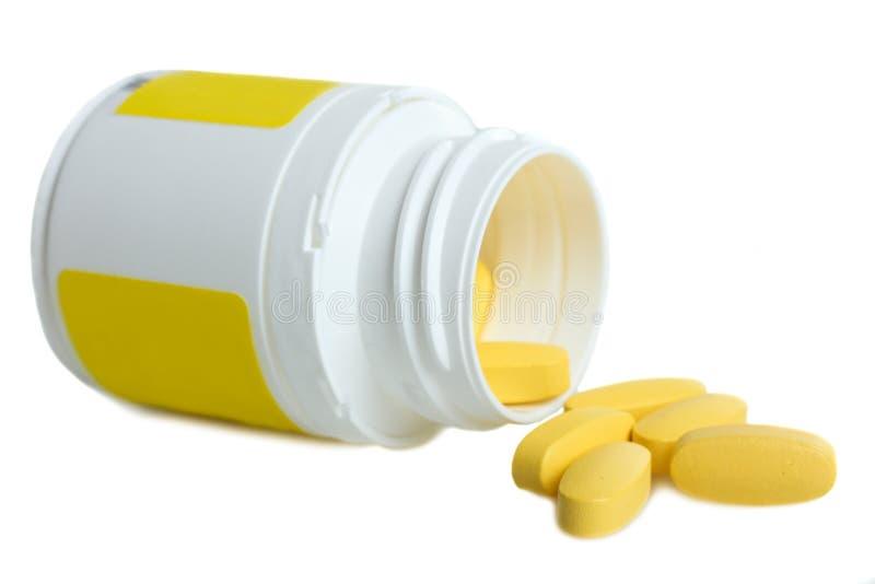 Gele vitaminen en fles stock fotografie