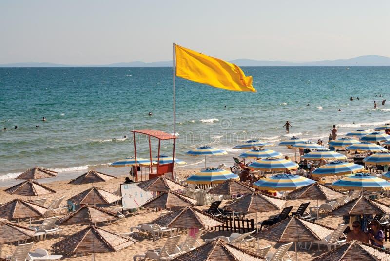 Gele vlag bij het overzeese strand stock foto's