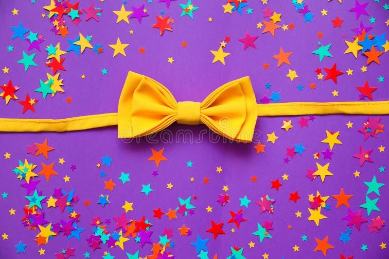 Gele vlinderdas op een purpere achtergrond stock foto's
