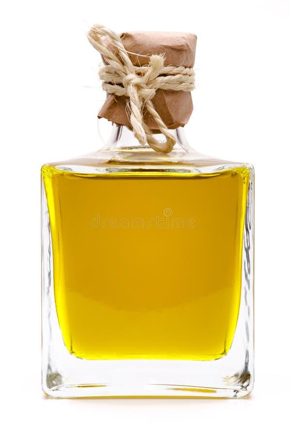 Gele vloeistof, olijfolie, in een kleine glasfles stock afbeeldingen