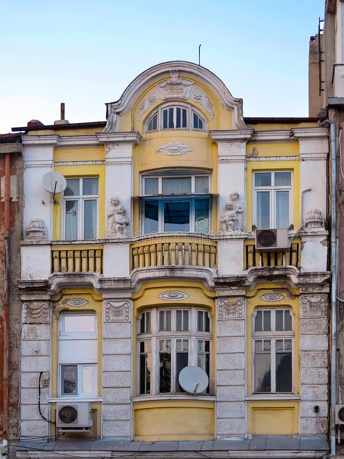 Gele voorgevel van het binnen gebouwde huis het eerste kwartaal van de laatste die eeuw met witte standbeelden van kinderen wordt royalty-vrije stock fotografie
