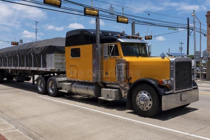 Gele vrachtwagen in een weg die een kleine Amerikaanse stad kruisen royalty-vrije stock foto's