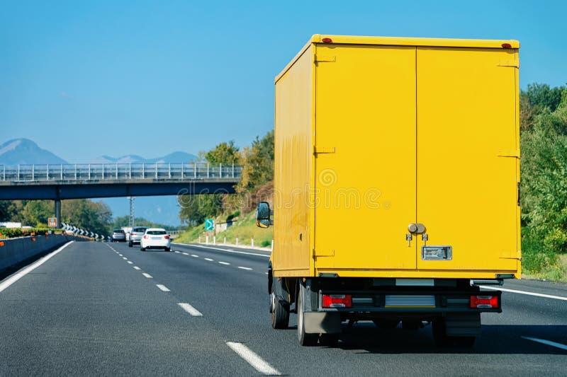 Gele vrachtwagen op weg in Italië stock afbeelding