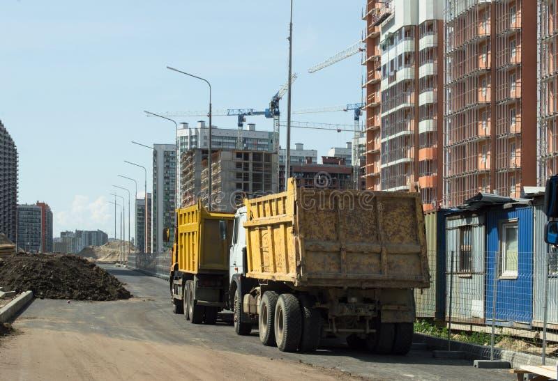 Gele vrachtwagenstribune op de wegen dichtbij de bouwwerf stock foto's