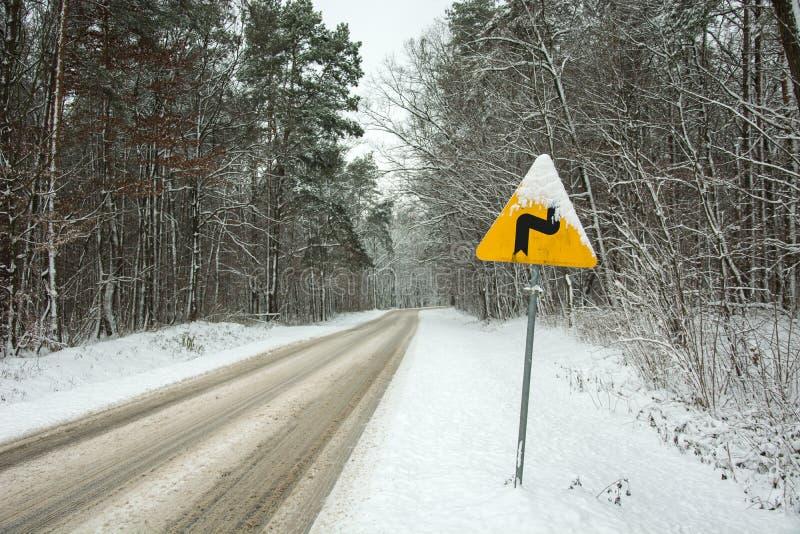 Gele waarschuwingsverkeersteken - gevaarlijke krommingen die, eerste juist - zich door de sneeuwweg door het bos bevinden - de wi royalty-vrije stock afbeeldingen