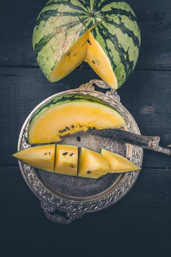 Gele watermeloen, plak van watermeloen op een verzilverd tafelgerei en mes op een donkere houten achtergrond Verticaal schot royalty-vrije stock afbeeldingen