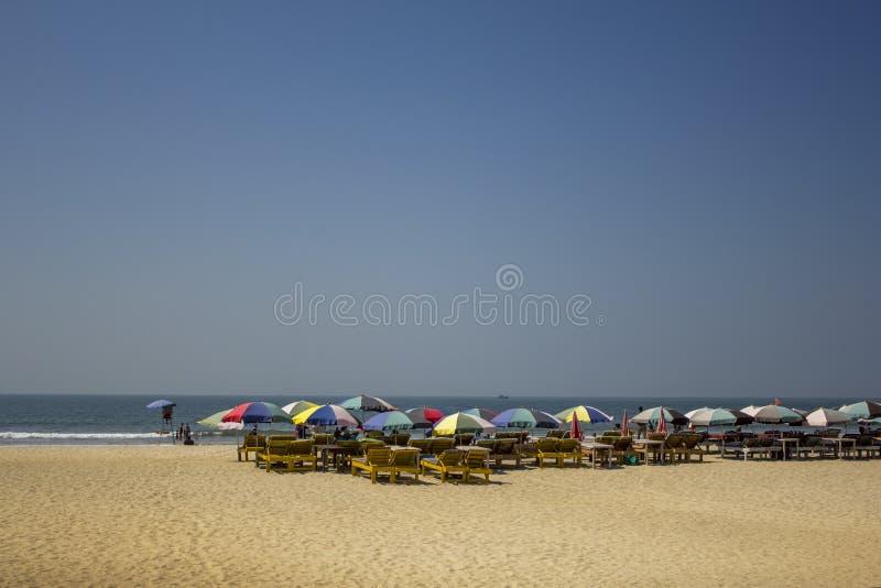 Gele zonlanterfanters onder multi-colored strandparaplu's op het zand tegen de oceaan onder een duidelijke blauwe hemel royalty-vrije stock foto's