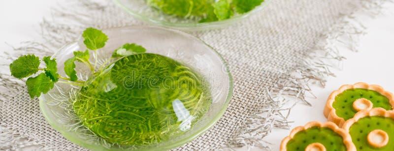 Geleia verde com as folhas de hortelã no vidro em um guardanapo de linho em um fundo branco fotos de stock