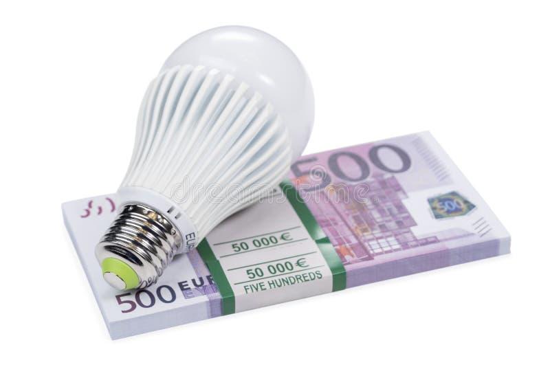 Geleide lamp op een bundel van geld royalty-vrije stock afbeelding